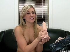 Light-complexioned newbie chats on the couch, gets naked and sucks on a dildo